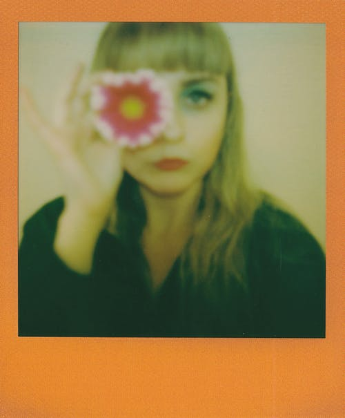Instant Photo of Woman in Black Shirt Holding Pink Flower