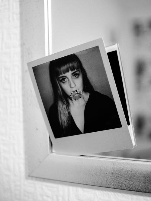 Instant photo of woman with blooming flower in mouth