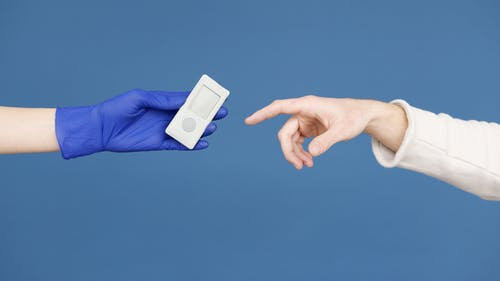 Person Holding White Card on Blue Textile