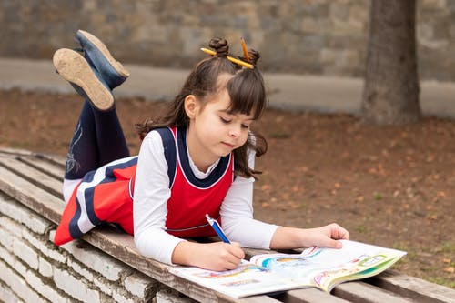 Girl in White and Red Long Sleeve Shirt Sitting on Bench Reading Book
