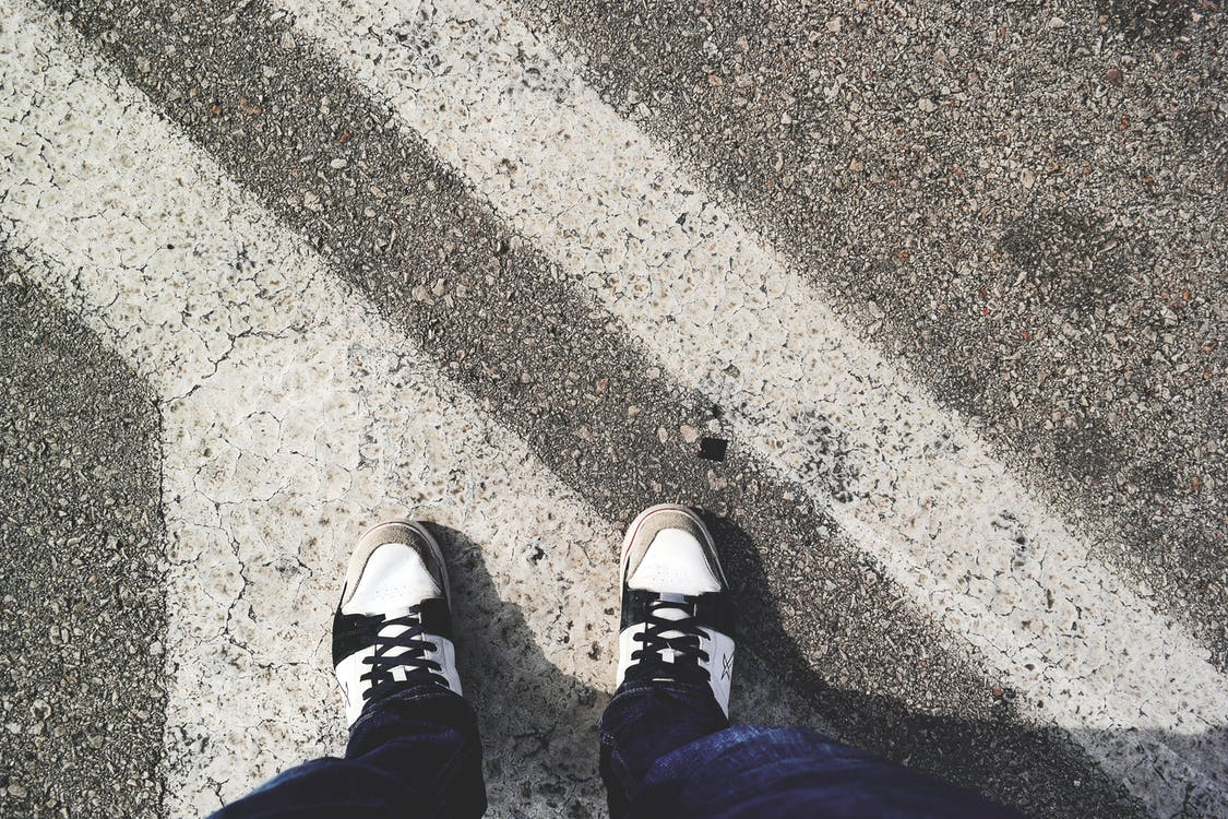 Man in White and Black Sneakers Standing Outdoor during Daytime
