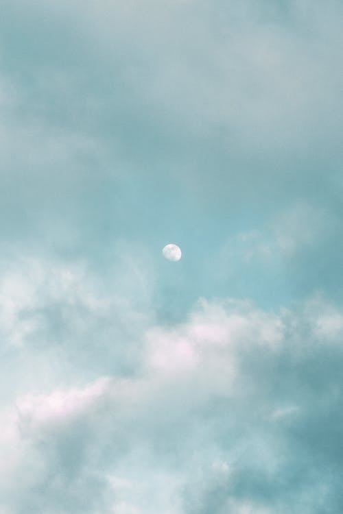 Light moon in blue sky with clouds