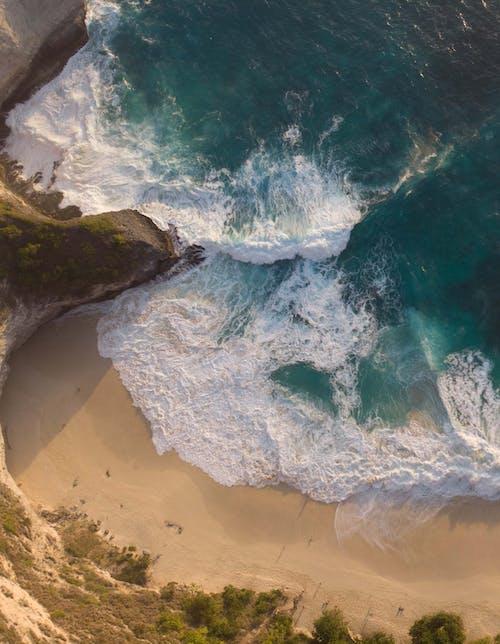 Amazing scenic sea washing sandy coast with foamy waves