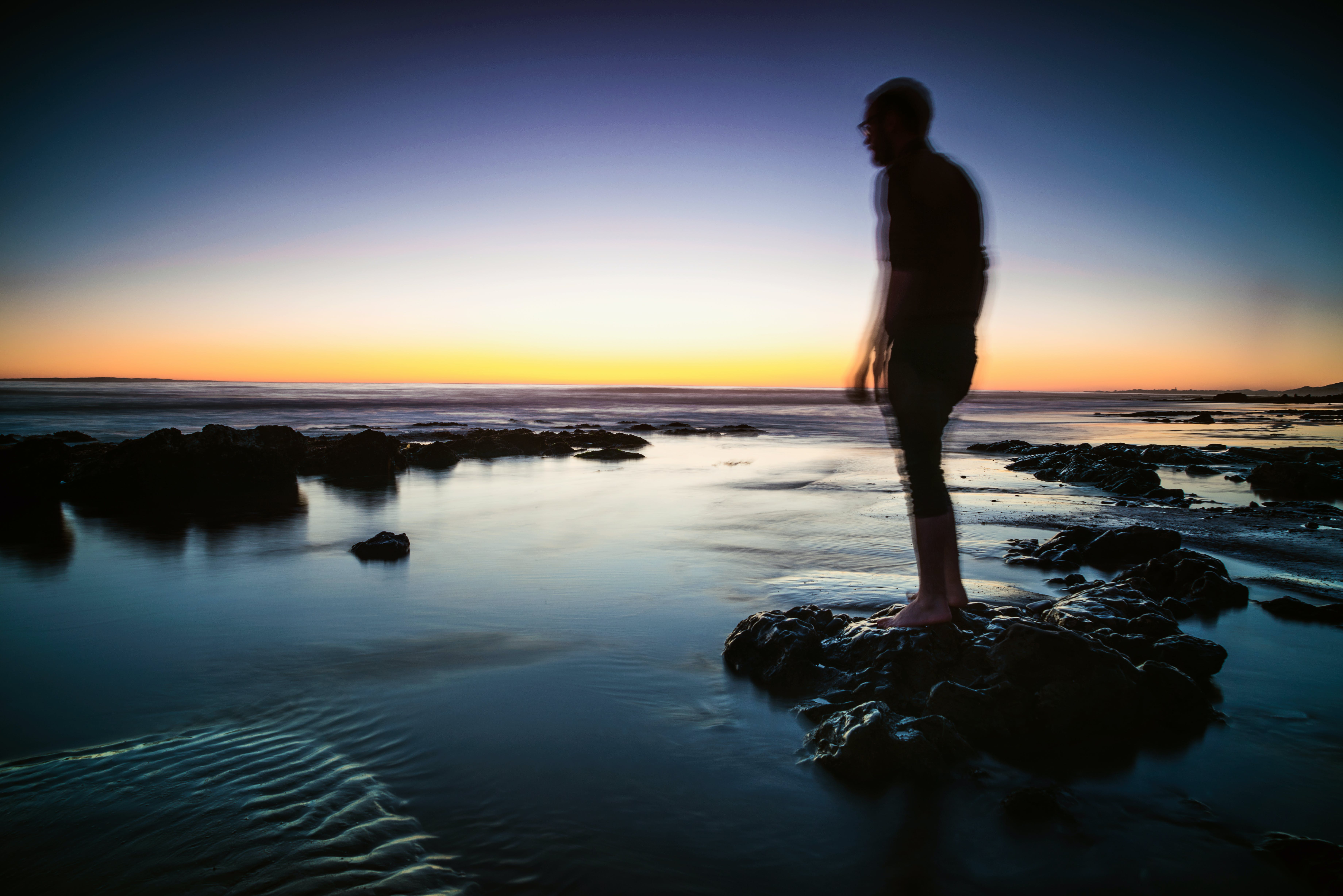 Silhouette of Man Standing on Rock Surrounded by Body of Water