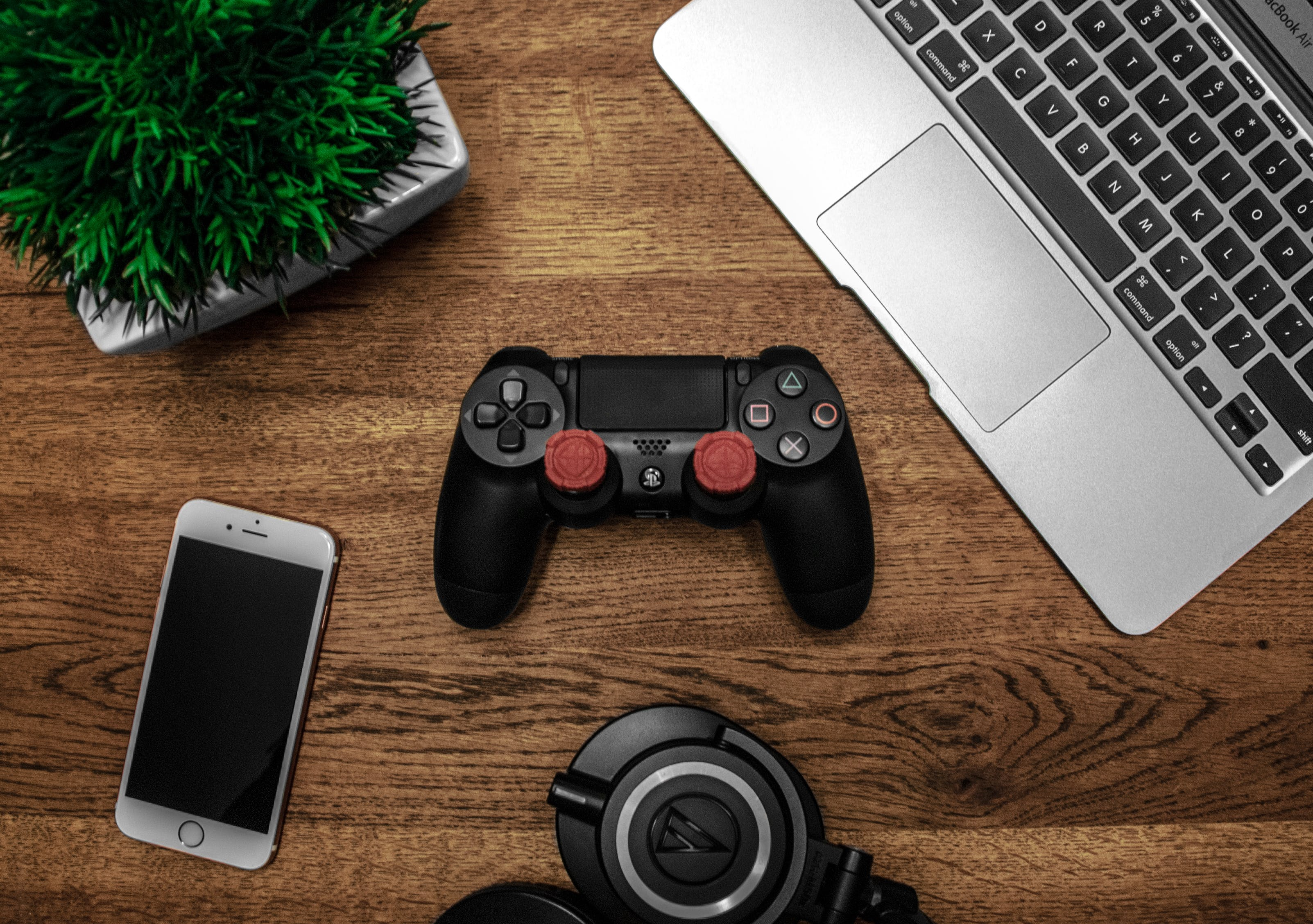 Silver Macbook Beside Black Sony Ps4 Dualshock 4, Silver Iphone 6, and Round Black Keychain on Brown Wooden Table