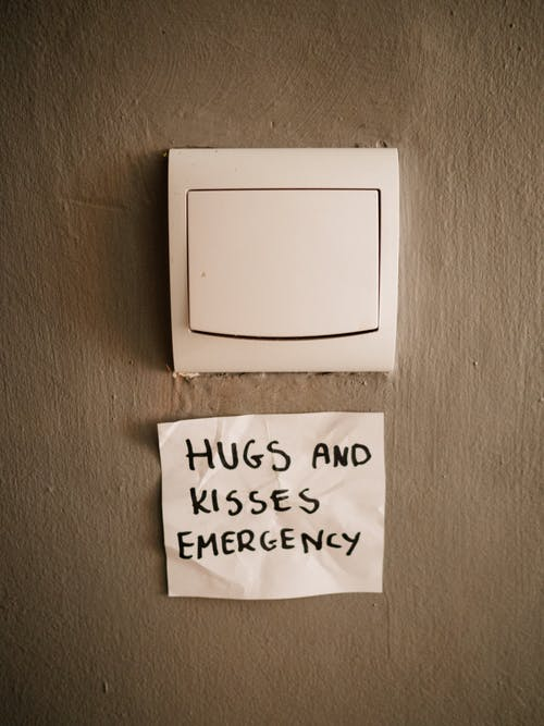 Lighting switch on wall near attached paper with Hugs and Kisses Emergency inscription