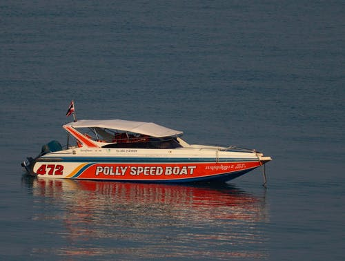 Contemporary motorboat decorated with flag and moored on calm rippling seawater in peaceful nature in daylight
