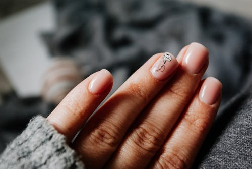 Crop faceless woman showing manicure with nail art