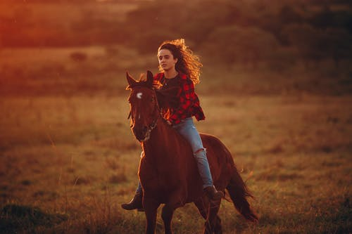 Young woman riding horseback in countryside