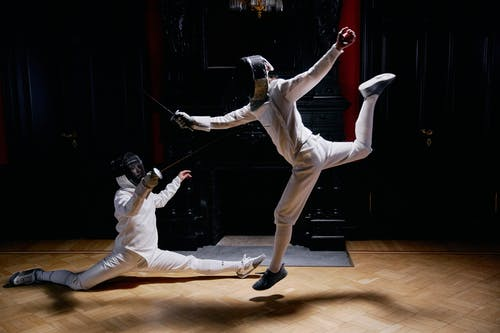 Two Men In Fencing Suits and Practicing With Swords