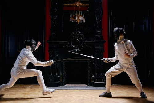 People in Playing Fencing
