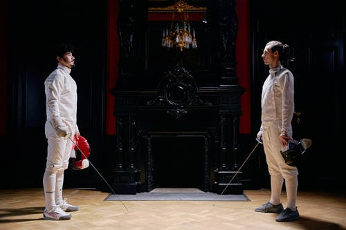Men in White Long Sleeves and White Pants Holding Silver Fencing Sword