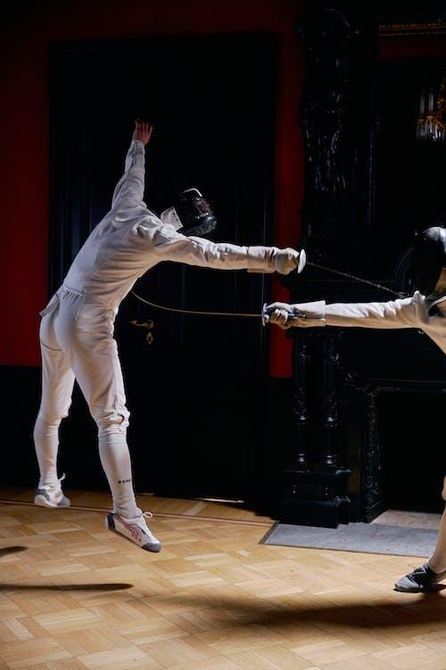 People in White Long Sleeves and Black Helmet Playing Fencing