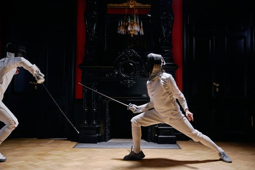 Person in White Long Sleeves Holding Silver Metal Rod Playing Fencing