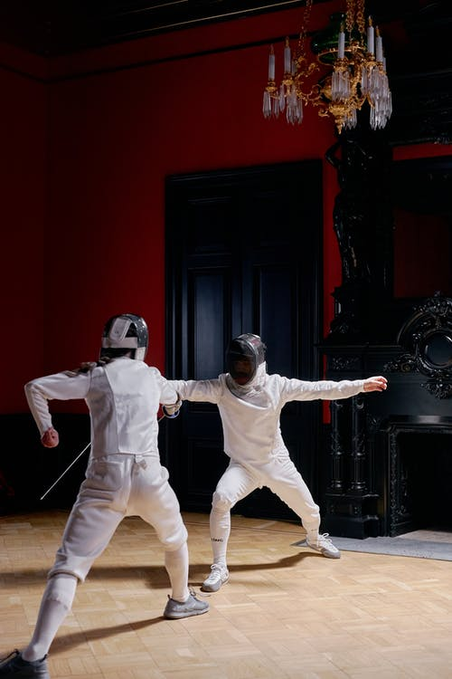Two Men In fencing Suit Practicing With Sword