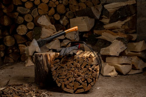 Pile of Firewood With Axe On A Tree Stump