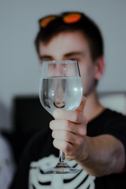 Anonymous young guy holding glass of water