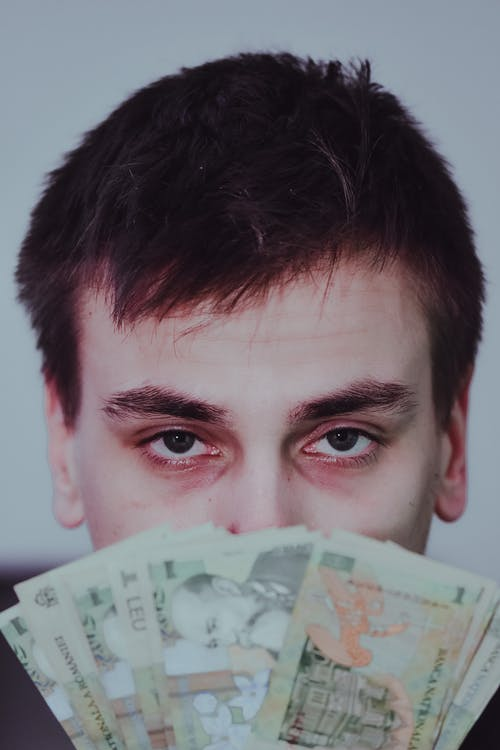 Serious guy showing stack of leu banknotes and looking at camera