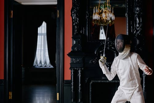 Man in White Fencing Suit Holding A Sword