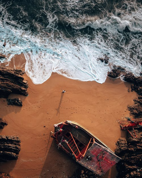 Amazing drone view of unrecognizable traveler standing on sandy beach washing by powerful foamy sea near old wooden boat and rocky formations on sunny day