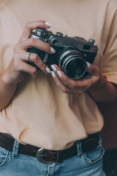 Faceless woman taking pictures on vintage photo camera