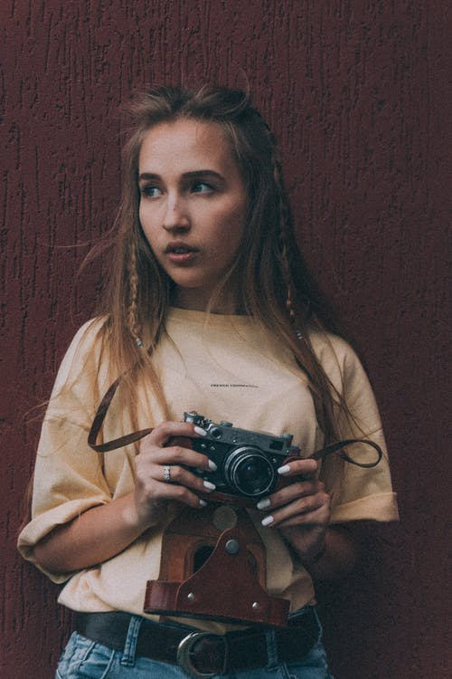 Thoughtful young female millennial with ling bond hair in stylish outfit using vintage photo camera and looking away against brown background