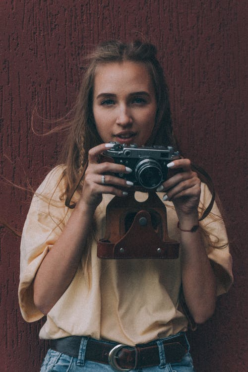 Positive young lady with long hair in stylish outfit smiling while taking pictures on vintage photo camera against brown background
