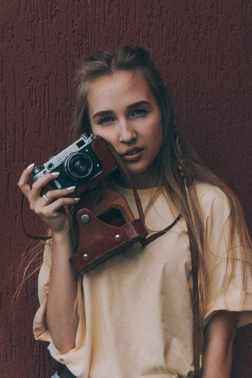 Confident young woman standing near brown wall with vintage photo camera in hand