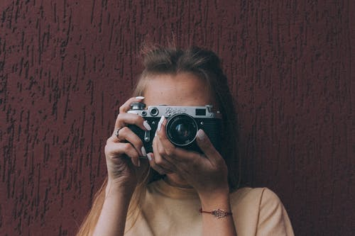 Unrecognizable woman focusing while taking pictures on vintage camera