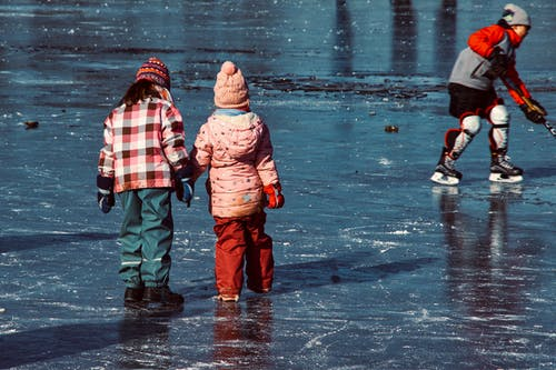 Hockey player with unrecognizable girlfriends on rink outdoors