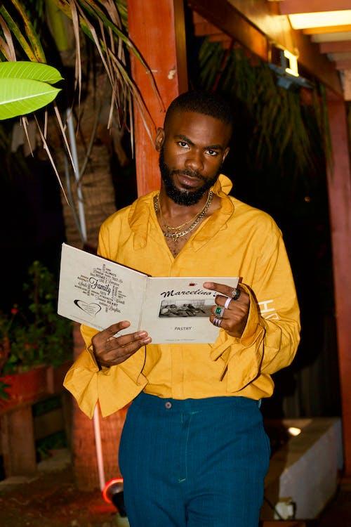 Man in Yellow Dress Shirt Holding White Printer Paper