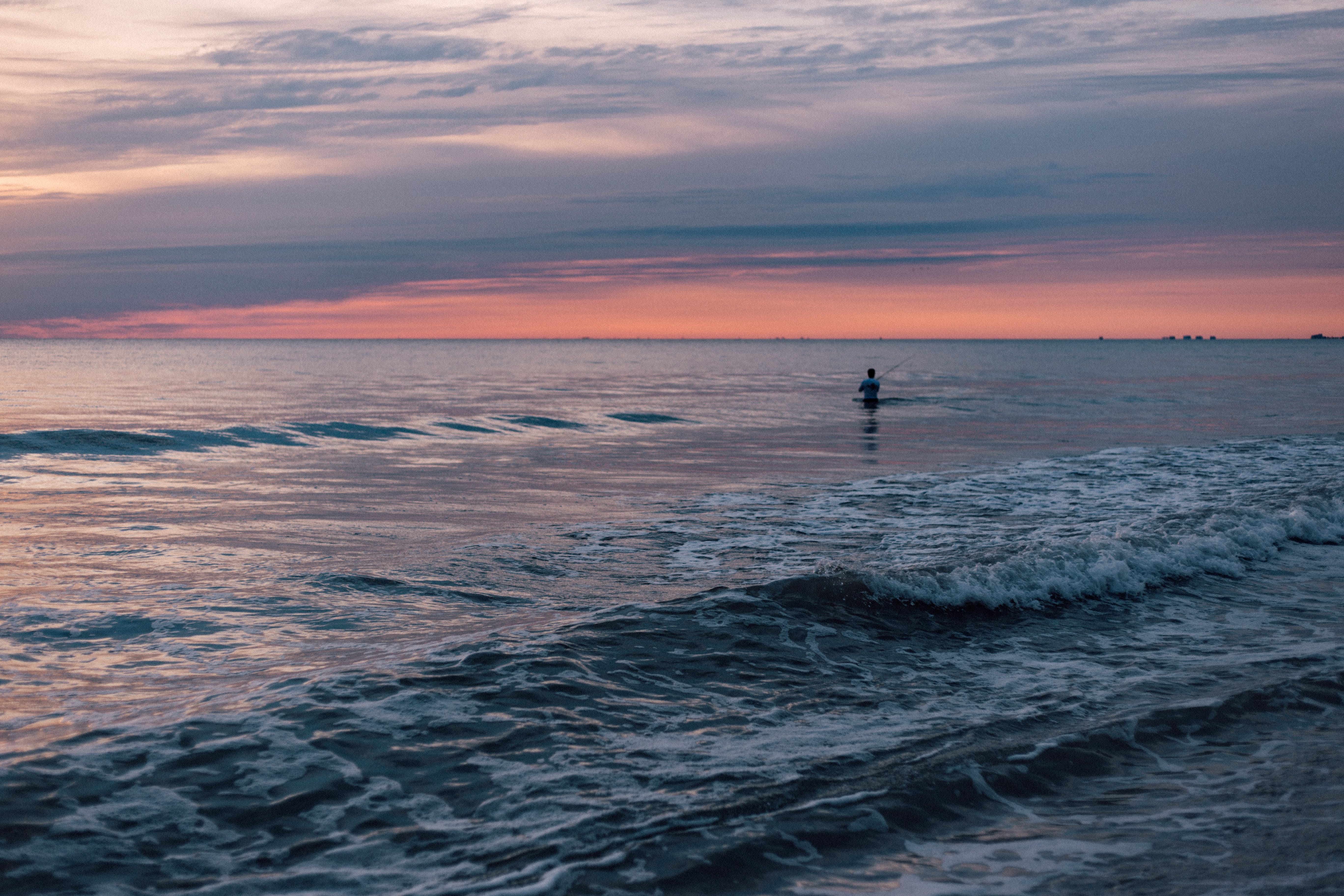 Person Standing in the Sea during Sunset