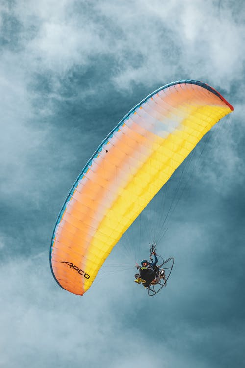 Anonymous traveler practicing paragliding in cloudy blue sky