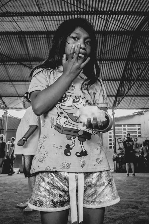 Ethnic teen girl licking fingers while eating in poor shelter