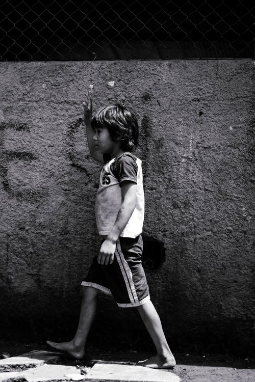 Black and white side view full body of little poor boy walking near shabby concrete wall