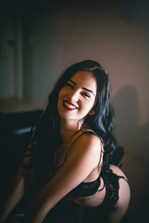 Sensual cheerful young female in black underwear looking at camera and smiling in dark room