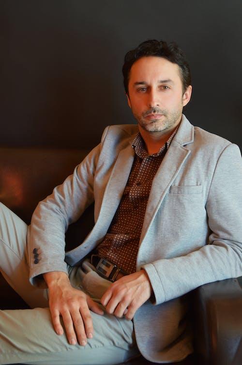 Serious man in elegant suit sitting on sofa