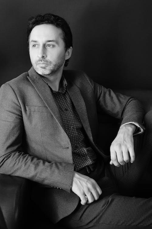 Elegant man in suit sitting on sofa
