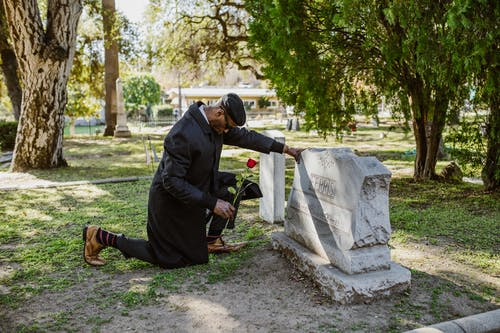 A Man in Black Clothes Kneeling Before a Tombstone
