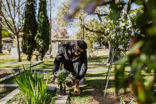 A Man Putting Flowers on the Ground