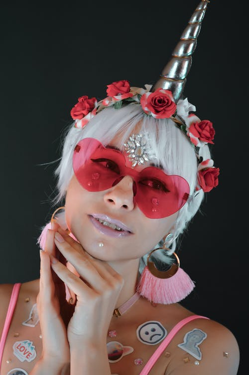Smiling female in heart shaped sunglasses and stickers on skin wearing unicorn horn and wreath against black background