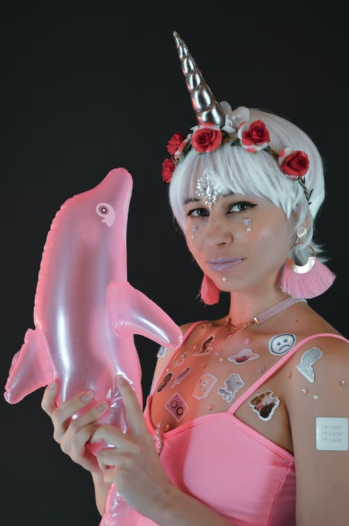 Young female model with creative makeup and stickers on skin wearing wig with horn holding inflated dolphin against black background
