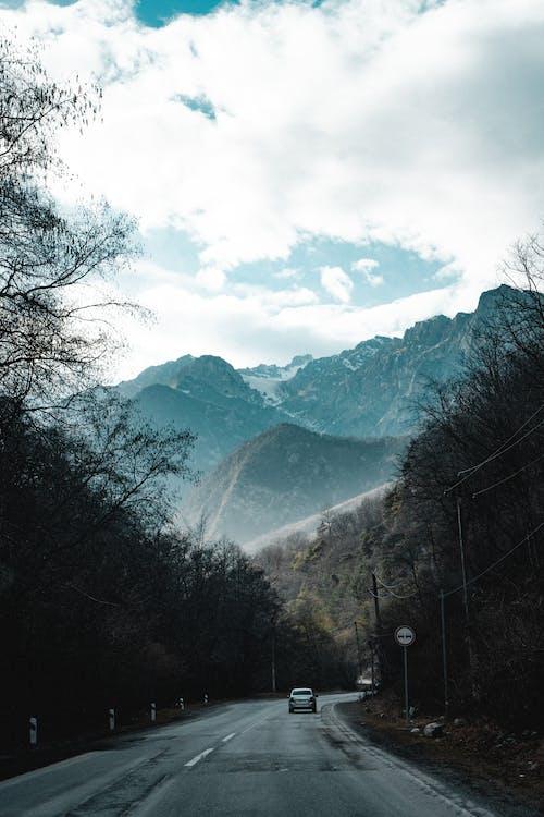 A Car Passing Through a Mountain Road