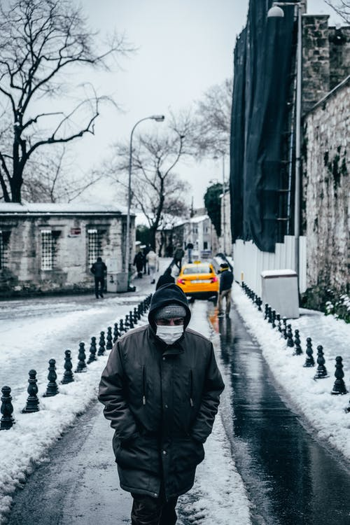 Man in protective mask strolling on walkway covered with snow on street with people on cold winter day in city