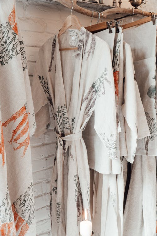 Robe and textiles with ornament on hangers indoors