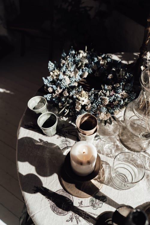 High angle of flaming candle against vase and glasses on table with blossoming flowers and shadows in sunlight