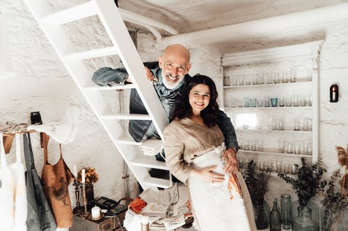 Smiling ethnic male embracing charming expectant female beloved in apron while looking at camera in house