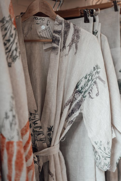 Assorted textiles and bathrobe with vegetable ornament and paper tag hanging on wooden rack in shop