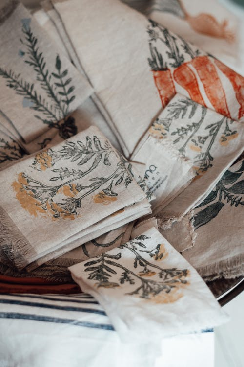 Collection of folded natural fabric napkins with flower and vegetable ornament with fringes on edges