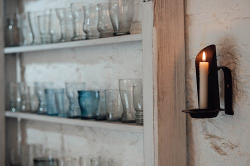 Flaming candle against shelves with glass vases indoors